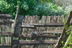 old wooden lopsided fence. time effect. rural scene - stock photo