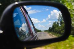 advance travelling on rural roads. car riding. rear-view mirror - stock photo