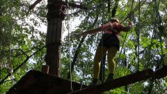 Climber move the ladder stretched between trees in the amusement rope park. Stock Footage