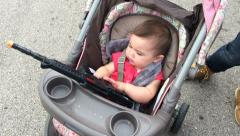 Young child in stroller playing with toy gun Stock Footage