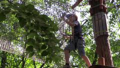 Climber move the ladder stretched platform on tree in the amusement rope park. Stock Footage