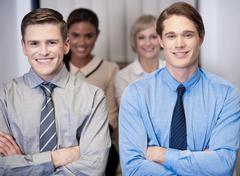 Stock Photo of Cheerful work team posing, arms crossed.