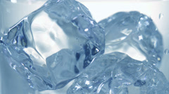 Pouring clear cold water into a glass with ice cubes. Slow motion Stock Footage