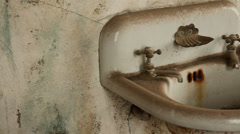 Dirty Sink in Abandoned Neglected Building with Antique Steam Radiator - stock footage