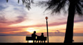 Father and Daughter Sit on the Beach against the Sunset. HD Footage