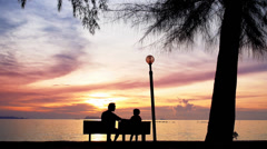 Father and Daughter Sit on the Beach against the Sunset. Stock Footage