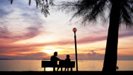 Stock Video Footage of Father and Daughter Sit on the Beach against the Sunset.