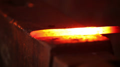 Blacksmith forging red hot iron on anvil, extreme closeup - stock footage