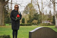 Woman grieving at cemetery holding flowers Stock Photos