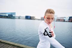 Female jogger monitor her progress on smartphone Stock Photos