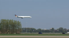 AMSTERDAM AIRPORT SCHIPHOL- Plane descends,  lands on runway parallel to highway Stock Footage