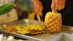 A man slicing pineapple in Thai market Stock Footage