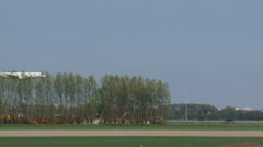 AMSTERDAM SCHIPHOL - Plane descends behind row of trees and lands on runway Stock Footage