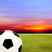 soccer ball with green grass field against sunset sky - stock photo