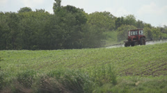 Fertilize agriculture down hill rural tractor spray rural field toxic chemical  Stock Footage