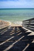 stairs to destination - wood stairs to the beach - stock photo