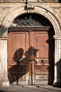 Old european sturdy wood doors with arch Stock Photos