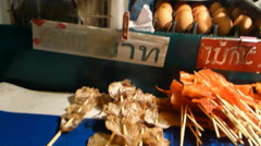 Stall selling grilled squid, pad thai in a night bazaar at Chiang Mai, Thailand. Stock Footage
