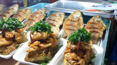 Stall selling Num Tok Phla (tilapia fish) at a market, Chiang Mai, Thailand. Stock Footage