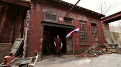 Master blacksmith stands in entryway of his historic shop, slider, wide shot Stock Footage