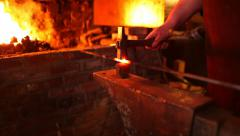 Blacksmith removes iron rod from fire, begins to forge on anvil, medium shot Stock Footage