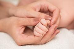 Baby's hand gripping adult finger Stock Photos