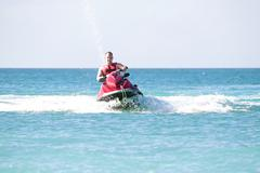 Young guy cruising on a jetski on the caribbean sea Stock Photos