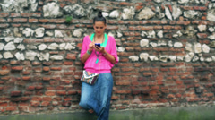 Woman with cellphone standing against brick wall, stedicam shot Stock Footage