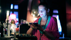 Woman with cellphone sitting in a pub, steadycam shot Stock Footage