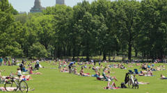 People sun bathing picnic on park lawn in Central Park - stock footage
