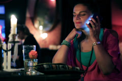Woman flirting on cellphone in a pub, steadycam shot Stock Footage