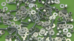 Nuts, washers and bolts rotating on a green background. Stock Footage