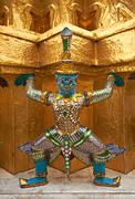 Colorful demon supporting golden stupa Stock Photos