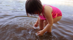 Cute Little Girl  Rinses Her Sandy Hands Off In Water Stock Footage
