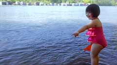 Cute Chatty Little Girl Points To Water, Then Fills Her bucket Stock Footage