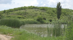 Beautiful landscape lake pond hill mountain vegetation reed green peaceful place Stock Footage