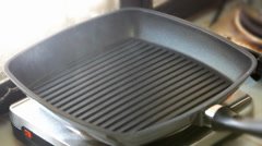 Close up of a grill pan smoking with heat while preparing to cook some food Stock Footage