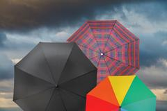 open umbrellas with storm grey clouds - stock photo