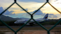 Airplane picks up speed to take off the ramp behind the fence at sunset Stock Footage
