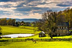 pond and house on a farm in rural york county, pennsylvania. - stock photo