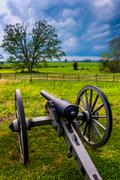 Storm clouds over a cannon in gettysburg, pennsylvania. Stock Photos