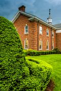 Storm clouds over bushes and a building at the lutheran seminary in gettysbur Stock Photos