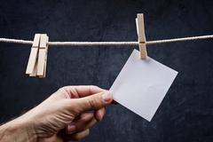 Hand picking blank note paper attached to rope with clothes pins Stock Photos