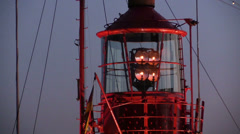Rotating lighthouse at dusk in harbor Stock Footage