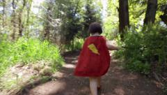 Little Girl Runs Away From Camera In Her Superhero Cape - stock footage