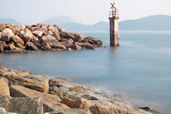 Lighthouse on a Rocky Breakwall: A small lighthouse warns of a rough shoreline. Stock Photos