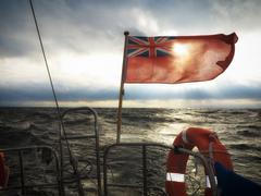 British maritime ensign flag boat and stormy sky Stock Photos