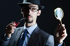 Detective with magnifying glass and pipe - stock photo