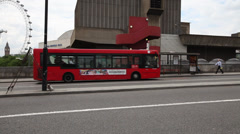 London Red Bus stops at bus stop, london eye in distance Stock Footage