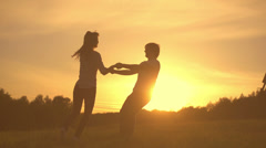 Romantic young couple silhouette, dancing, holding hands and spinning around - stock footage